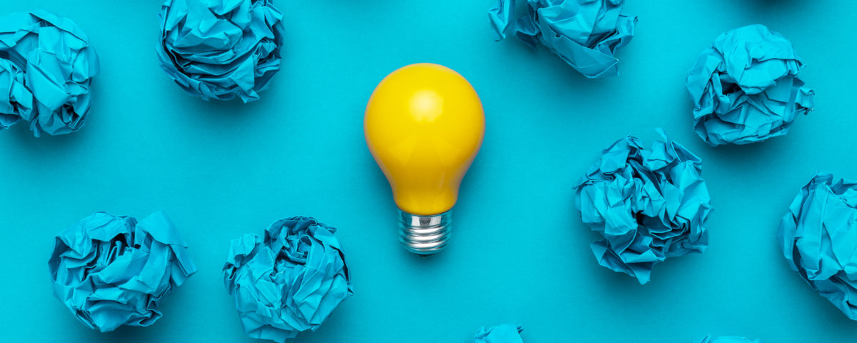 New Idea Concept With Blue Crumpled Office Paper And Light Bulb.